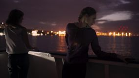 Silhouette of two attractive young women traveling on a ship at night. Girlfriends on the boat. In Odessa stock footage