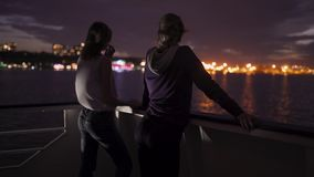 Silhouette of two attractive young women traveling on a ship at night. Girlfriends on the boat. In Odessa stock video footage
