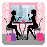 Silhouette of two beautiful girls talking. In a cafe Royalty Free Stock Photo
