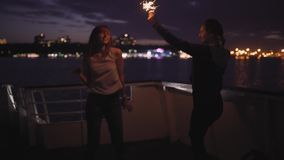 Silhouette of two beautiful young women dancing on ship deck at night. Girlfriends on the boat. Silhouette of two attractive young women traveling on a ship at stock video