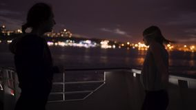 Silhouette of two beautiful young women dancing on ship deck at night. Girlfriends on the boat. Silhouette of two attractive young women traveling on a ship at stock footage