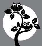 Silhouette of two black owls in a tree. Manufacturing or interior royalty free illustration