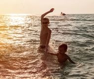 Silhouette of two boy jumping in sea stock photo