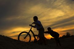 Silhouette Two boys are helping friend. Silhouette Two boys are helping to push the bike up the hill Stock Photography