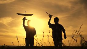 Silhouette of two boys running with airplanes at sunset stock video