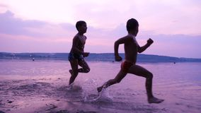 Silhouette of two boys running along the shore of river. Against sunset, slow motion stock footage
