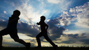 Silhouette of two boys running on field against sunset. Slow motion stock video footage