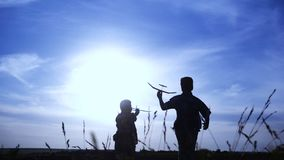Silhouette of two boys running with airplanes at sunset stock video footage