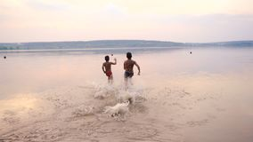 Silhouette of two boys running into the water. Of the river against sunset, slow motion stock video footage