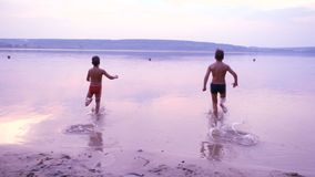 Silhouette of two boys running into the water. Of the river against sunset, slow motion stock video