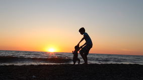 The silhouette of two boys throwing stones into the sea at the beach stock video