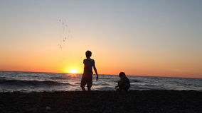 The silhouette of two boys throwing stones into the sea at the beach stock video footage