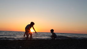The silhouette of two boys throwing stones into the sea at the beach stock footage