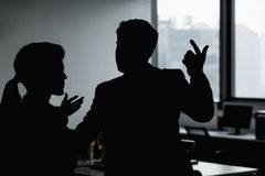 Silhouette of two business people gesturing and arguing in the office Royalty Free Stock Images