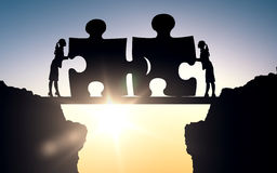 Silhouette of two business women connecting puzzle Stock Image