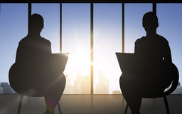 Silhouette of two business women with laptop Stock Photos