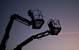 Silhouette of two cherry pickers Royalty Free Stock Photos