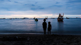 Silhouette of two children. Looking to fishing boat at the beach during sunset Stock Photos