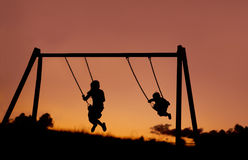 A silhouette of two children swinging outside at sunset. Stock Images