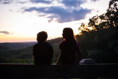 Silhouette of two children watching sunset stock photography