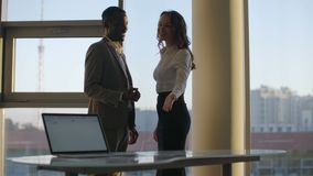 Silhouette of two company employees talking to each other in front of large panoramic window. city skyline background stock video footage