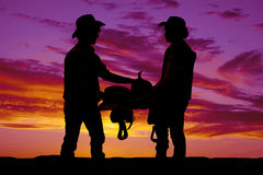 Silhouette of two cowboys holding a saddle in the sunset Stock Photos