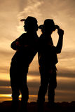 Silhouette of two cowboys standing back to back in the sunset Stock Images