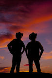 Silhouette of two cowboys standing in the sunset Stock Images
