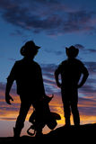 Silhouette of two cowboys in the sunset one hold saddle. Silhouette of two cowboys in the outdoors one has a saddle in his hands Stock Photo