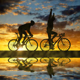 Silhouette of two cyclists riding a road bike Stock Image