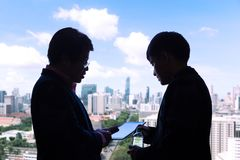 Silhouette of two executive businessmen discussing over a project on a computer tablet with city highrises and sky view in the ba. Silhouette of two executive stock images