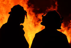 Silhouette two firemen in front bushfire flames. Silhouettes of a pair of brave firemen dressed in their uniform and safety gear with the raging flames of a huge Stock Images
