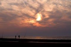 Silhouette of two fishermen Stock Photos