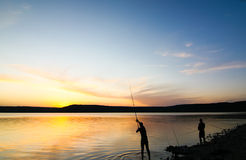 Silhouette of two fishermen at sunset. Two young men fishing at sunset. The sky is clear and blue. The sun hides behind the horizon. It's quiet around Stock Image