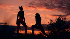 Silhouette of two fitness woman profile stretching at sunrise with the sun in the background stock footage