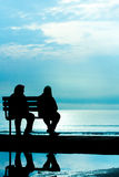Silhouette of two friends sitting on wood bench near beach stock image