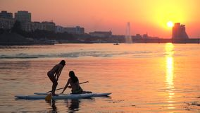 Silhouette of two girls that communicate standing on sap boards while a guy swims by on a jet ski, slow motion. Girls rest on the river during sunset with a stock footage