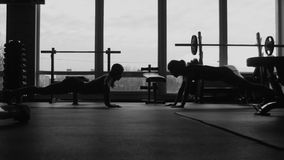 Silhouette, two girls do push-ups together in a gym. Wide movement shooting stock video footage