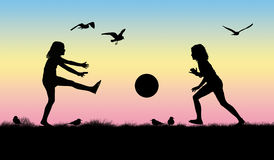Silhouette of two girls playing with a ball. On the grass with some seagulls around them, sunset sky on the background Royalty Free Illustration