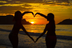 Silhouette of two girls at sunset Stock Images