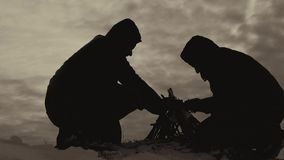 Silhouette two guys friends in the wood in fall, organising the camp fire, helping each other, team work, dventures