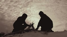 Silhouette two guys friends in the wood in fall, organizing the camp fire, helping each other, team work, dventures