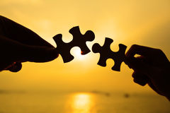 Silhouette of two hands connect jigsaw together Stock Images