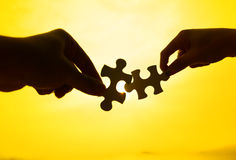 Silhouette of two hands connect puzzle together. With golden background Royalty Free Stock Photography