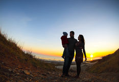 Silhouette of two happy adults and a child Stock Images