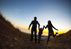 Silhouette of two happy adults and a child Stock Photos