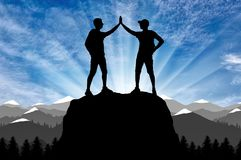 Silhouette of two happy climber conquered the top. stock image