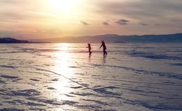 Silhouette of two ice skating people at lake Baikal frozen surface on sunset. Winter tourism concept Royalty Free Stock Image