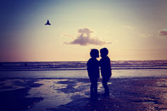 Silhouette of two kids, kissing on the beach Royalty Free Stock Photo