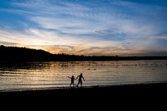 Silhouette of two kids near the lake at sunset. Beautiful sunset. Evening. Two kids holding hands walking in the water. Two birds in the distance Stock Photos